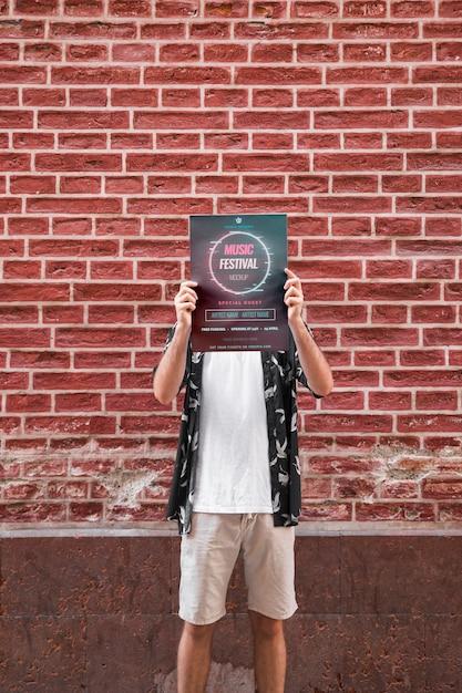 レンガの壁の前にポスターのモックアップを提示する男 無料 Psd
