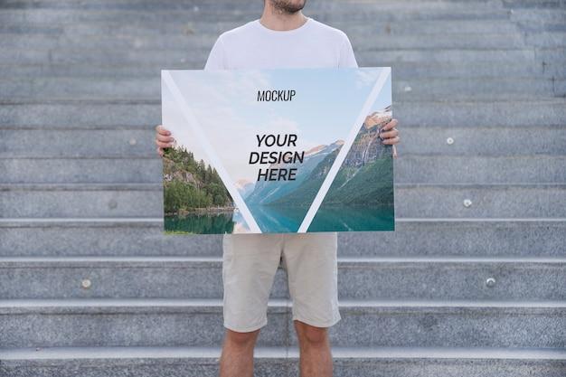 Человек, представляя плакат макет перед лестницей Бесплатные Psd