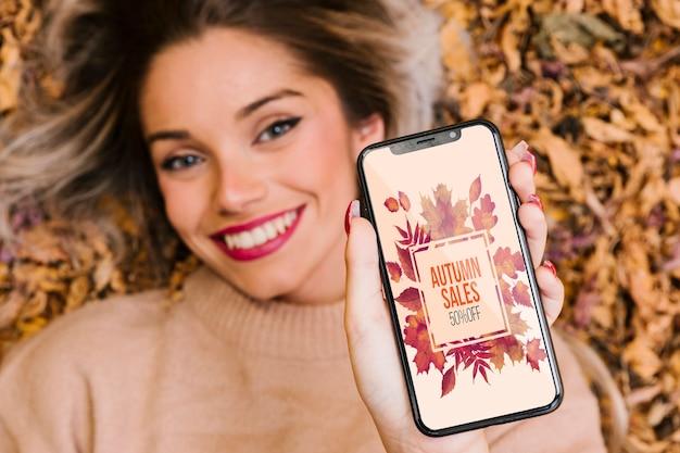 Модель показывает свой телефон и улыбается Бесплатные Psd