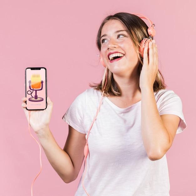Смеется молодая женщина с наушниками, проведение макет мобильного телефона Бесплатные Psd
