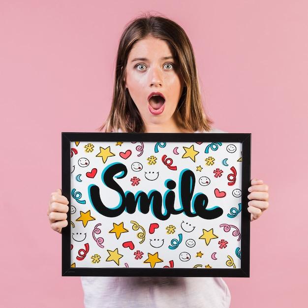 Удивленная молодая женщина показывает макет кадра Бесплатные Psd