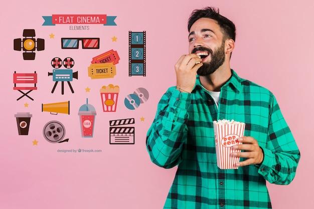 Молодой человек ест попкорн рядом с элементами кино Бесплатные Psd