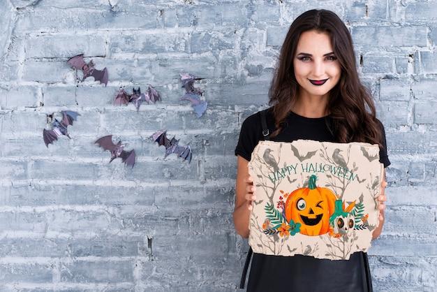 Женщина держит открытку с вырезанной тыквой на хэллоуин Бесплатные Psd