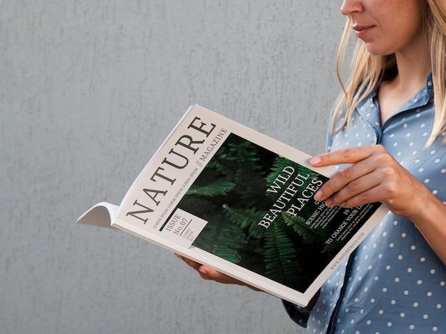 Боковой вид женщина, держащая журнал природы Бесплатные Psd