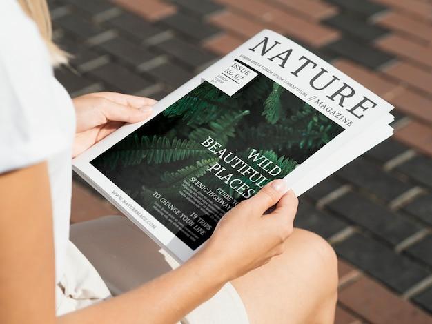 モックアップの野生の自然雑誌を保持している手 無料 Psd