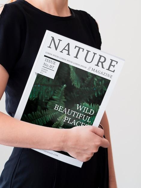 Женщина в черном платье держит журнал макет Бесплатные Psd