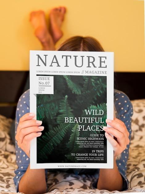 Женщина в постели показывает журнал о природе Бесплатные Psd