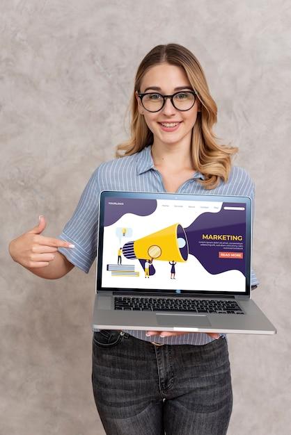 Женщина держит ноутбук и указывая на него Бесплатные Psd