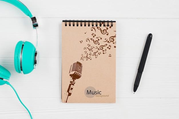 Блокнот для музыкальных нот с наушниками рядом Бесплатные Psd
