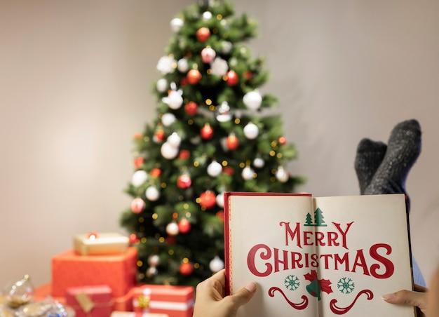 ぼやけたクリスマスツリーとメリークリスマスの本 無料 Psd