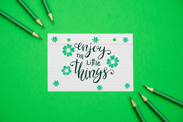 Наслаждайтесь цитатой на белой бумаге с цветами и зеленом фоне Бесплатные Psd
