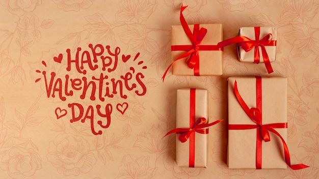包まれた贈り物の横にある幸せなバレンタインデーレタリング 無料 Psd