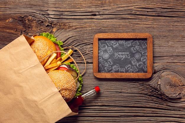木製の背景とフレームの木製の背景に紙袋のハンバーガーメニュー 無料 Psd