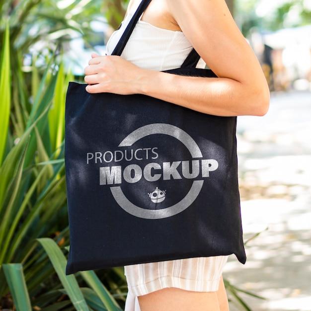 Боком женщина, держащая черный мешок макет Бесплатные Psd