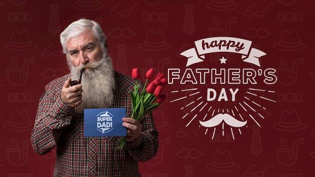 Отец держит картонный макет и цветы на бордовом фоне Бесплатные Psd