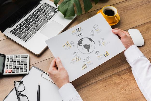 Офисный стол с человеком, держащим макет листа бумаги Бесплатные Psd