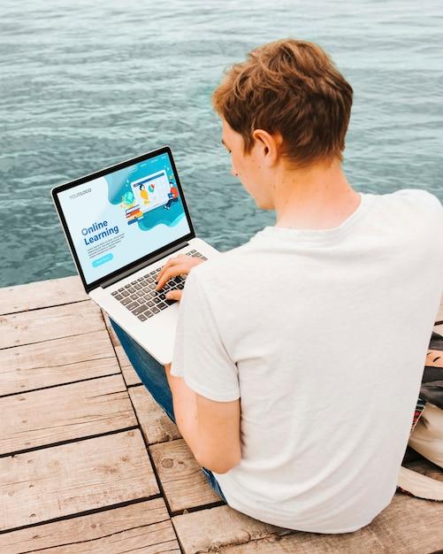 Студент с удовольствием работает онлайн на открытом воздухе Бесплатные Psd