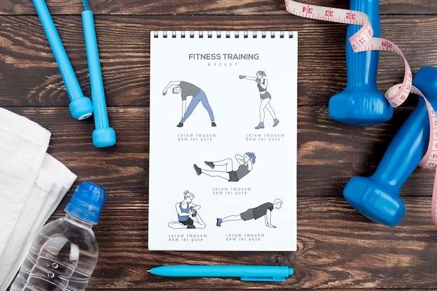 Вид сверху фитнес-тетради с гантелями и бутылкой с водой Бесплатные Psd