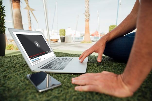 ノートパソコンとモバイルと屋外のクローズアップ男 無料 Psd