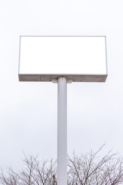 広告のための白い雲空とブランクの看板白いスクリーンポスターのモックアップ画像 Premium Psd