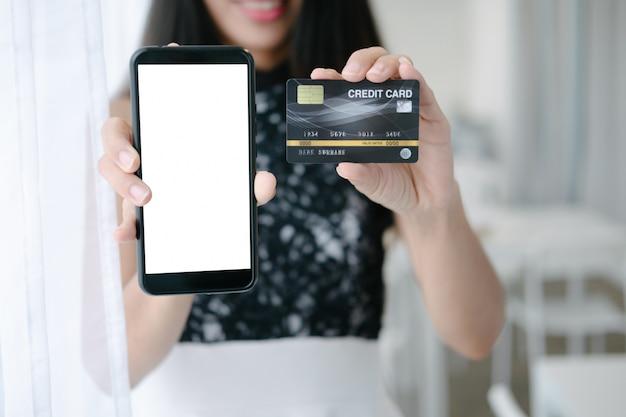 オンラインウェブサイトでスマートフォンでオンラインショッピングクレジットカードを保持している美しい女性のモックアップ Premium Psd