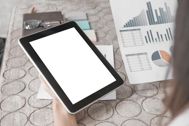 タブレットとオフィスでドキュメントを扱うビジネス女性を間近のモックアップ Premium Psd