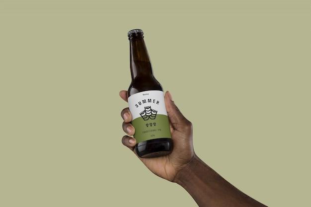 Рука держит бутылку пива макет Premium Psd
