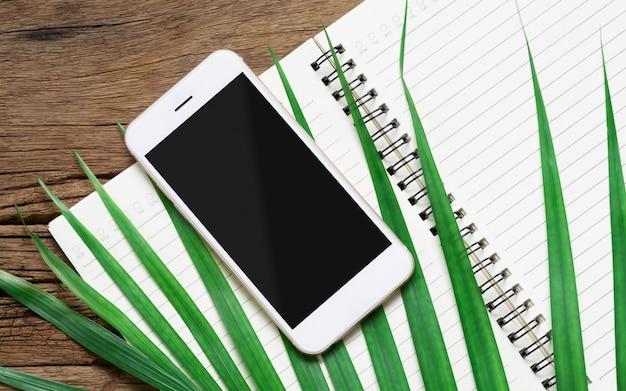 緑のヤシの葉とノートブックを開くと黒の空白のモックアップ画面で白いスマートフォン Premium Psd