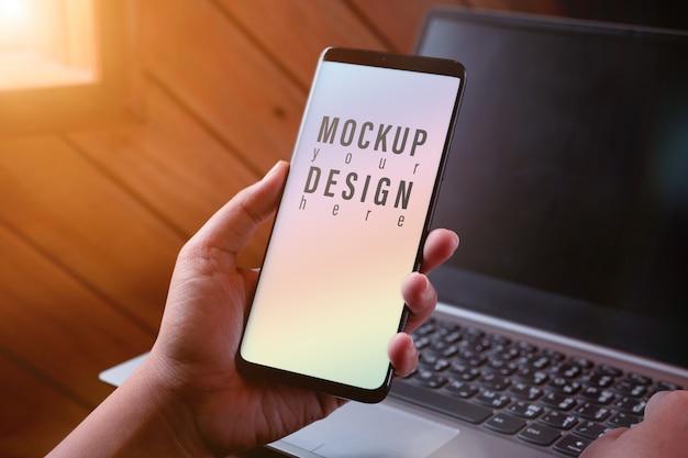 モックアップのスマートフォン画面。ぼやけたノートパソコンで現代のスマートフォンテクノロジーを使用して手を閉じる Premium Psd