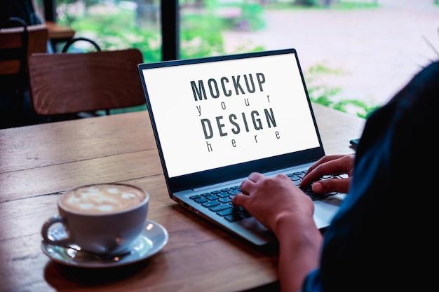 コーヒーショップでラップトップを使用して入力するビジネス女性のモックアップ画像。 Premium Psd