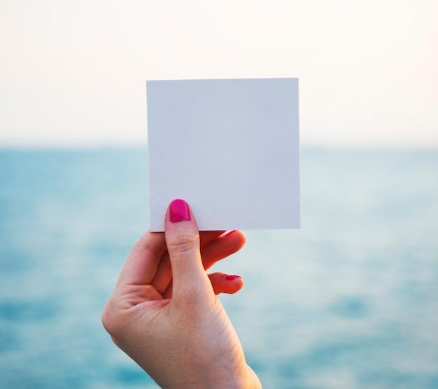 海の背景と穴の開いた紙のフレームを保持する手 無料 Psd