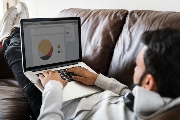 ソファーでラップトップを使用している男 Premium Psd
