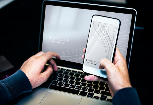 ラップトップと携帯電話のモックアップを使用しているビジネスマン 無料 Psd