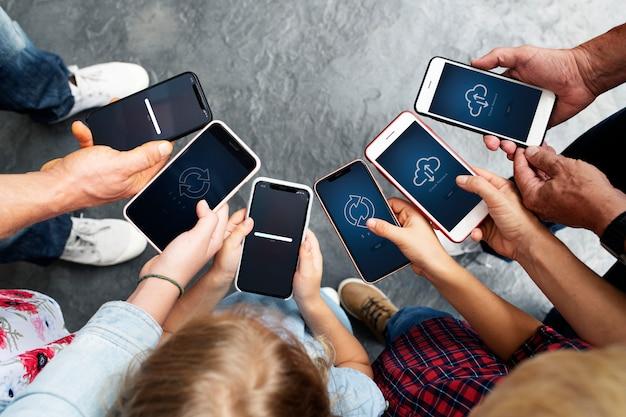 スマートフォンを見ている人々のグループ Premium Psd