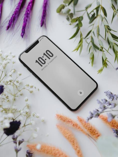 乾燥した色とりどりの花の束で囲まれた電話モックアップ Premium Psd