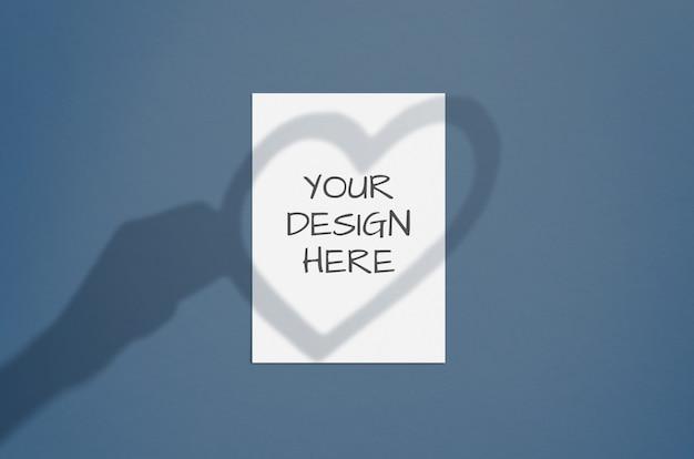 手と心の影のオーバーレイと空白の白い垂直紙。モダンでスタイリッシュなバレンタイングリーティングカードまたは結婚式招待状のモックアップ Premium Psd