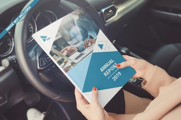 Мягкая обложка книги в руке на макете рулевого колеса автомобиля Premium Psd