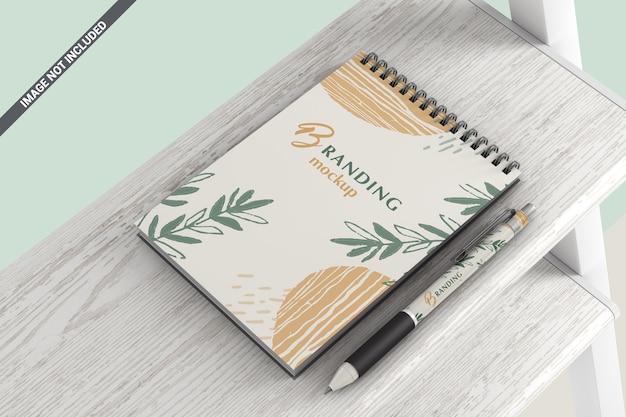 木製の棚のモックアップの上に横たわるペンとノート Premium Psd