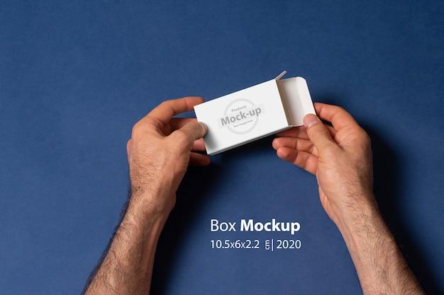 Мужчина руками открывает коробочку перед темно-синей поверхностью Premium Psd