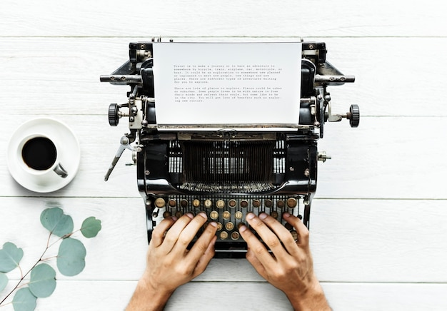 Aerial view of a man typing on a retro typewriter Free Psd