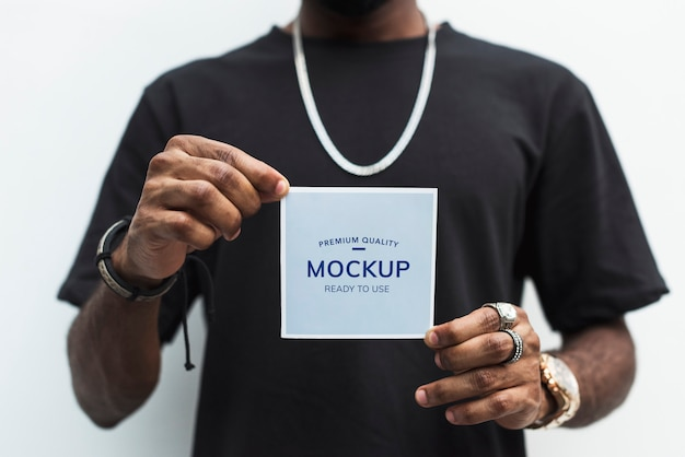 African man holding a photo paper mockup Free Psd