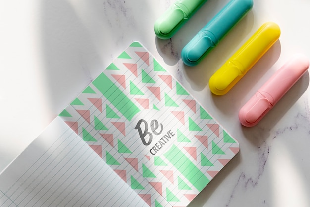 Agenda with markers beside on desk Free Psd