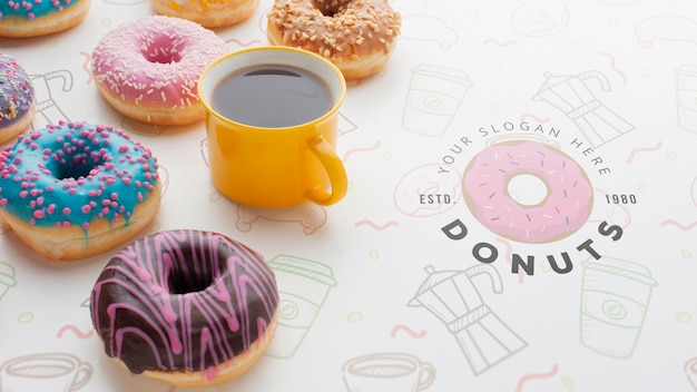 Disposizione di ciambelle colorate e caffè nero con mock-up Psd Gratuite