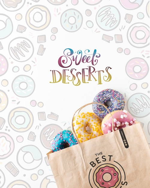 Arrangement of colorful donuts in paper bag with mock-up Free Psd