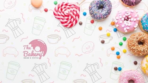 Disposizione di ciambelle colorate e dolci con mock-up Psd Gratuite
