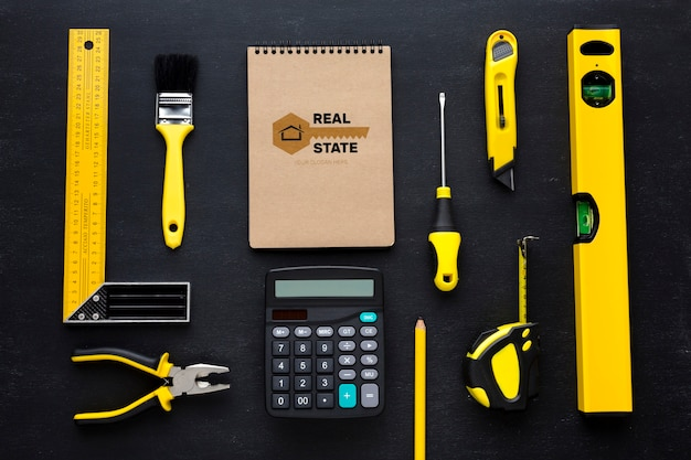 Arrangement of different repairing tools with notepad mock-up on black background Free Psd