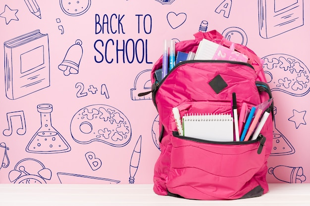 Arrangement with pink school bag and supplies Free Psd