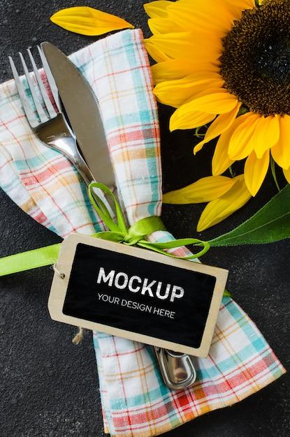 空のタグ、ナプキンとひまわりのカトラリーと秋のテーブルの場所の設定。 Premium Psd