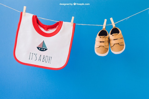 Baby mockup with bib and shoes on clothes line Free Psd