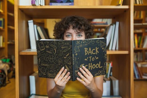 Di nuovo al concetto del banco con il libro di lettura della ragazza in libreria Psd Gratuite